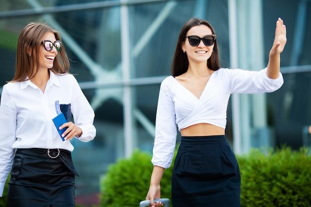 Twee vrouwen in de buurt van de luchthaven gaan met het vliegtuig