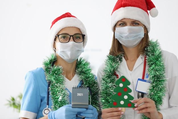 Twee vrouwen in de hoed en het klatergoud van de kerstman.