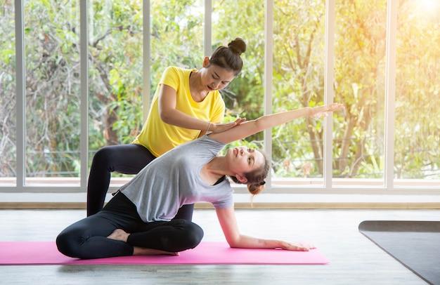 Twee vrouwen in de klas, ontspanningsoefening of yogales post-workout bij de raamstudio