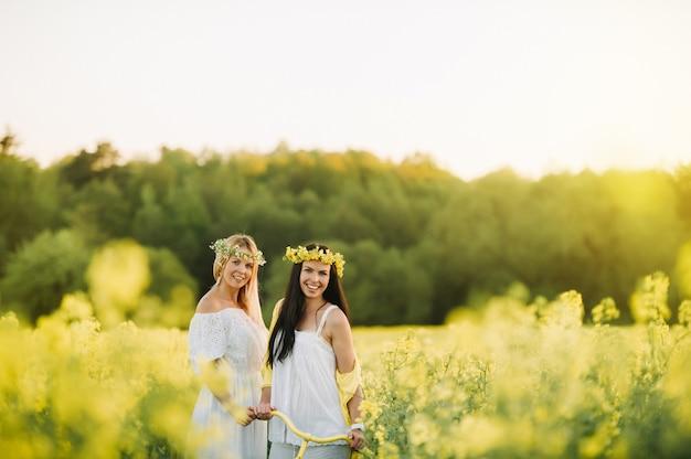 Twee vrouwen in een koolzaadveld met een fiets genieten van een vreugdevolle wandeling in de natuur.