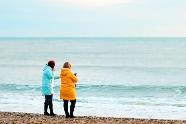 Twee vrouwen in lichte kleren staan op het strand en bewonderen het uitzicht. achteraanzicht. het concept van openluchtrecreatie.