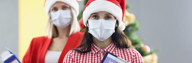 Twee vrouwen in medische beschermende maskers en hoeden van de kerstman houden mappen met documenten. jaarverslag bedrijfsconcept