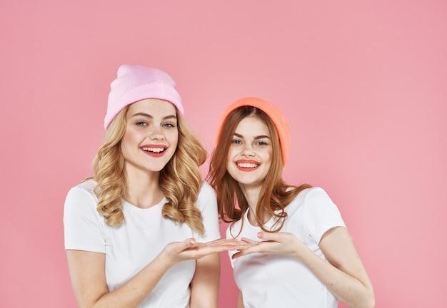 Twee vrouwen in modieuze kleding roze hoeden studio bijgesneden weergave.