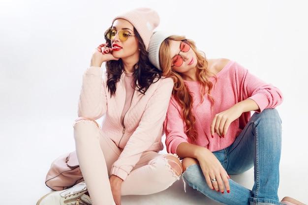 Twee vrouwen in mooie roze winteroutfit, roze hoeden en truien ontspannen op de vloer, plezier maken op een witte achtergrond.