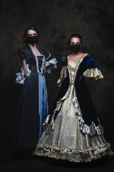 Twee vrouwen in renaissancejurk, gezichtsmasker en handschoenen, coronavirus, covid-19 beschermingsconcept.