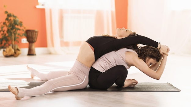 Twee vrouwen in sportkleding die yoga beoefenen, doen upavishta konasana bending en baddha konasana bending