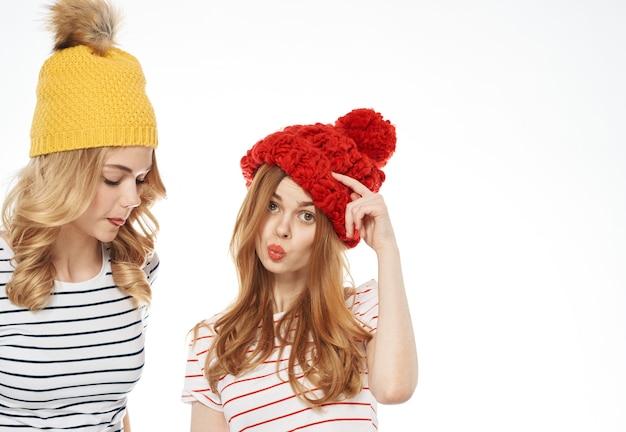 Twee vrouwen in veelkleurige hoeden knuffelen vriendschap communicatie mode bijgesneden weergave