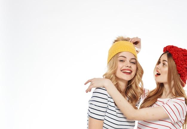 Twee vrouwen in veelkleurige hoeden omhelzen vriendschap communicatie mode