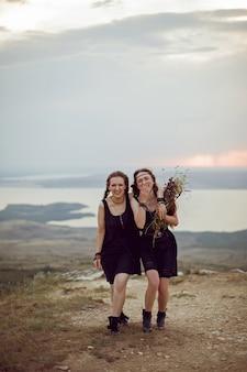Twee vrouwen in zwarte jurken lopen op de berg met een boeket bloemen in de zomer bij zonsondergang
