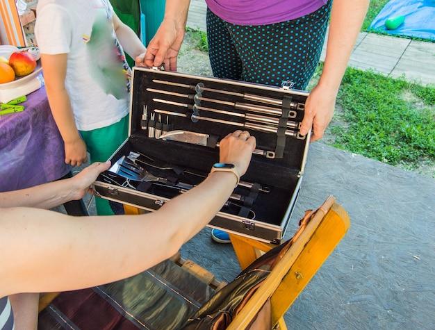 Twee vrouwen kijken naar een luxe barbecueset, in een geschenkverpakking.