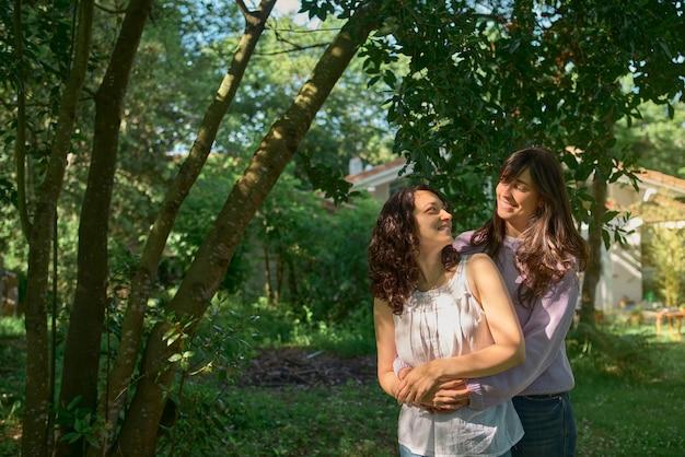 Twee vrouwen knuffelen verliefd en kijken elkaar glimlachend aan met bomen op de achtergrond