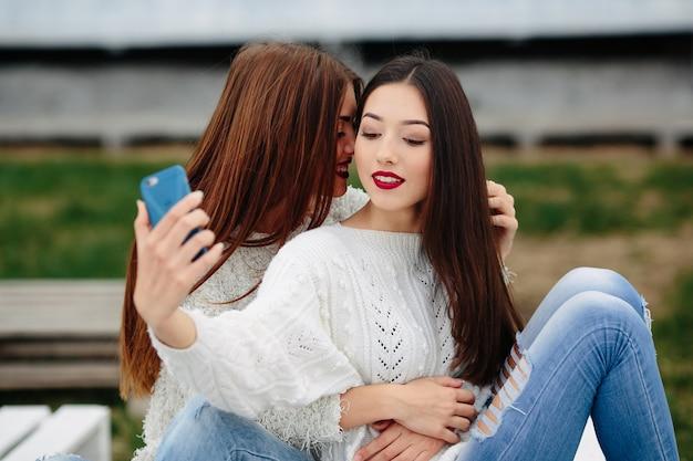 Twee vrouwen maken selfie op de bank in het park