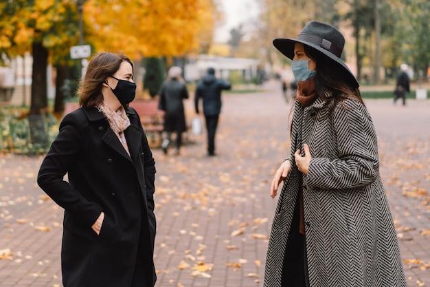 Twee vrouwen met beschermende maskers lopen in het park en bewaren een sociale afstand
