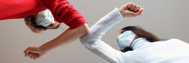 Twee vrouwen met beschermende medische maskers die elkaar aanraken met hun ellebogen veiligheidsregels tijdens