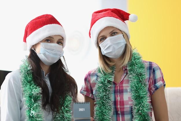 Twee vrouwen met een beschermend masker zitten naast elkaar en houden de kalender 2021 vast.