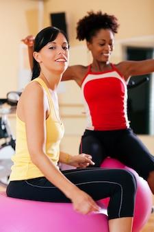 Twee vrouwen met fitness bal in de sportschool