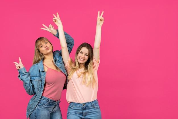 Twee vrouwen met handen die op roze achtergrond worden opgeheven