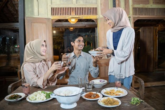 Twee vrouwen met hoofddoeken en een aziatische man die samen de eettafel opruimt na iftar