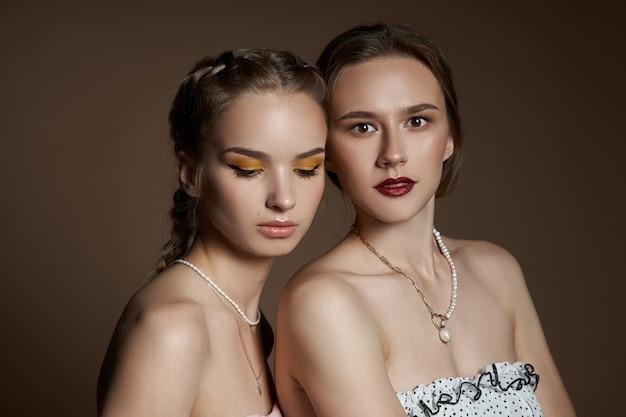 Twee vrouwen met kettingen om hun nek