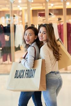 Twee vrouwen met plastic zakken op shopping spree