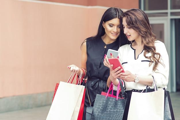 Twee vrouwen met smartphone en boodschappentassen