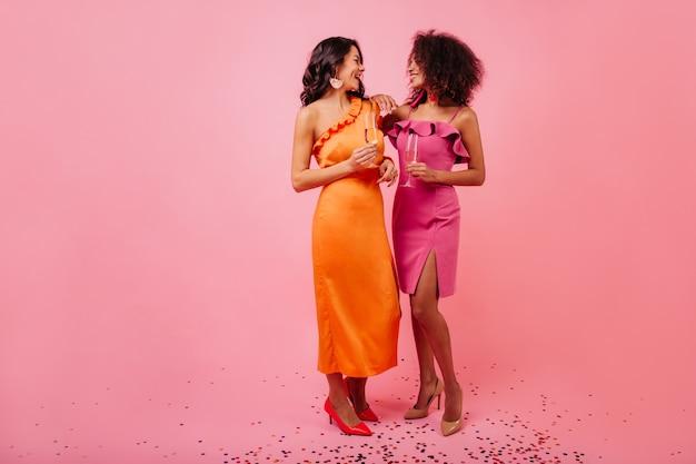 Twee vrouwen met wijnglazen praten op feestje