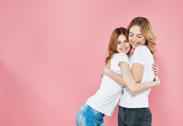 Twee vrouwen modieuze kleding vriendschap roze knuffels.