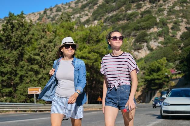 Twee vrouwen moeder en dochter tiener lopen op zonnige zomerdag op bergweg