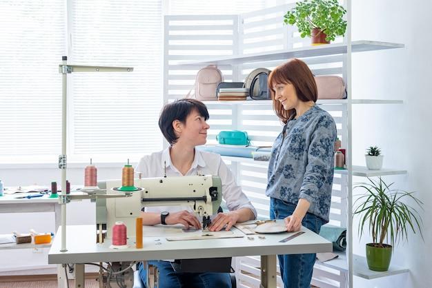 Twee vrouwen naait zakaccessoires op een naaimachine en communiceert