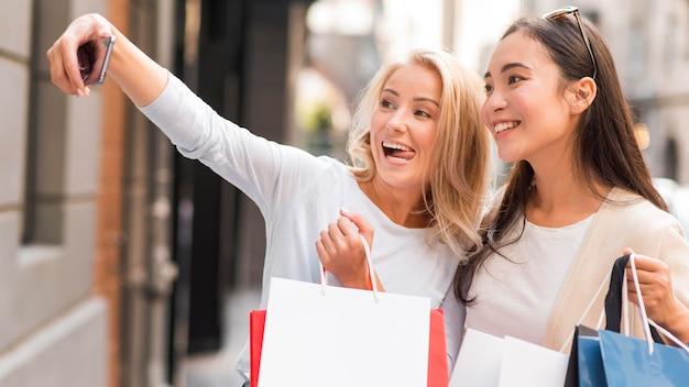 Twee vrouwen nemen selfie met veel boodschappentassen