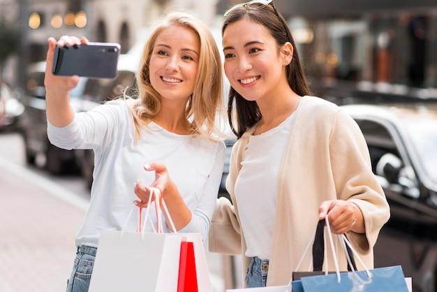 Twee vrouwen nemen selfie terwijl ze veel boodschappentassen vasthouden