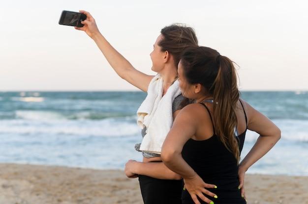 Twee vrouwen nemen selfie tijdens het trainen op het strand
