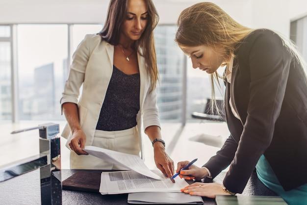 Twee vrouwen ondertekenen een contract dat zich in een modern appartement bevindt.