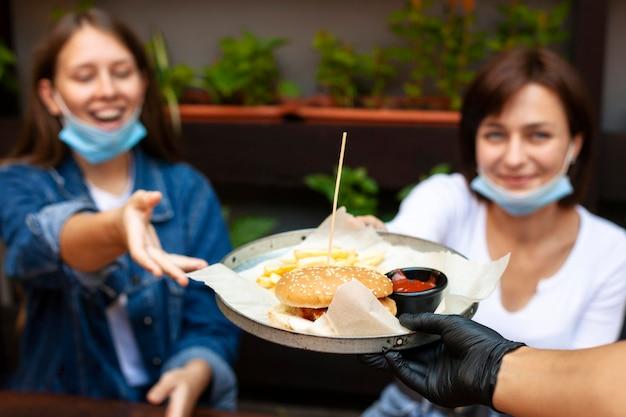 Twee vrouwen ontvangen hun bestelling voor fastfood