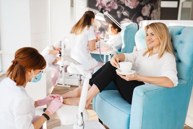 Twee vrouwen op pedicureprocedure in de schoonheidssalon. professionele schoonheidsspecialisten en vrouwelijke klanten