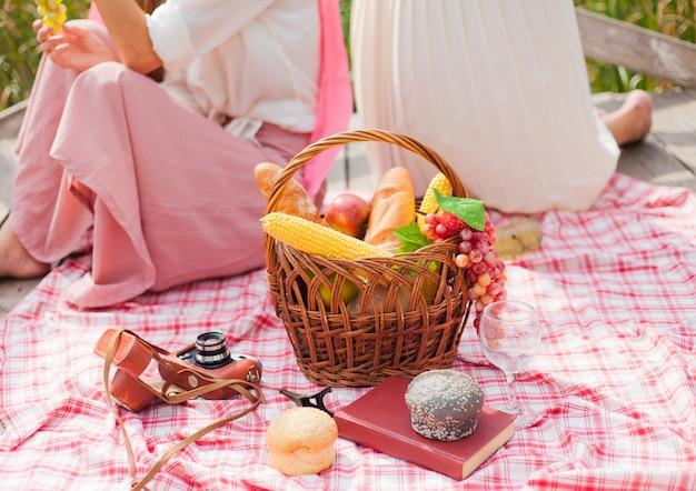Twee vrouwen picknicken buiten op een zomerse dag.