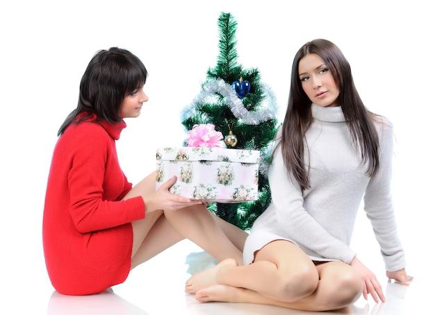 Twee vrouwen poseren in jurken zittend op de vloer in de buurt van een kerstboom. meisje geeft een vakantiegift