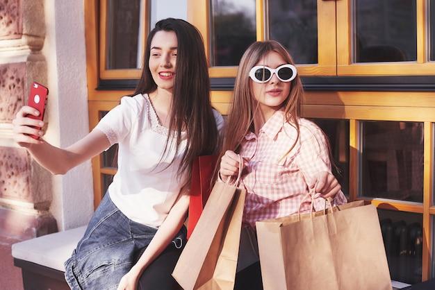 Twee vrouwen praten na het winkelen op straat bij het raam.