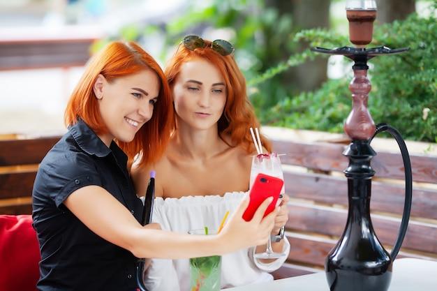 Twee vrouwen roken een waterpijp en genieten van cocktails in een café op straat.