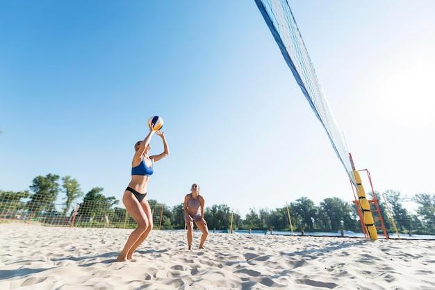 Twee vrouwen spelen volleybal aan het strand