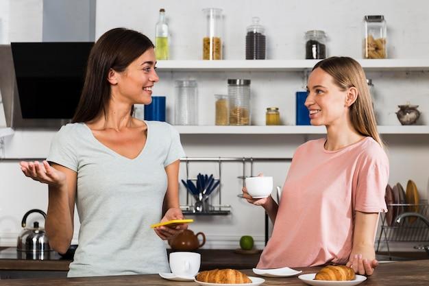 Twee vrouwen thuis chatten tijdens een kopje koffie