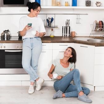 Twee vrouwen thuis in de keuken die bij koffie kletsen