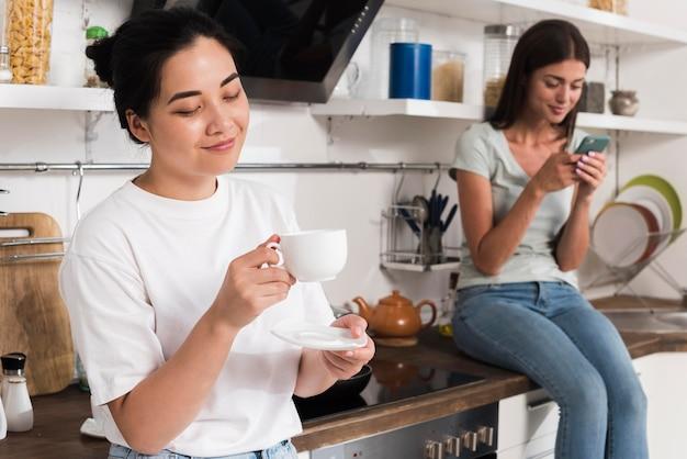Twee vrouwen thuis in de keuken met koffie en smartphone