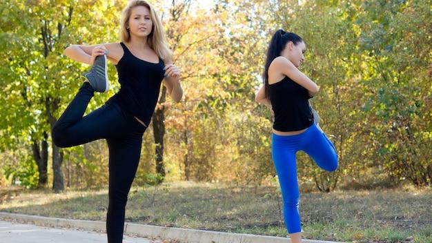 Twee vrouwen trainen samen buiten in een park, strekken en balanceren tijdens het opwarmen voor joggen