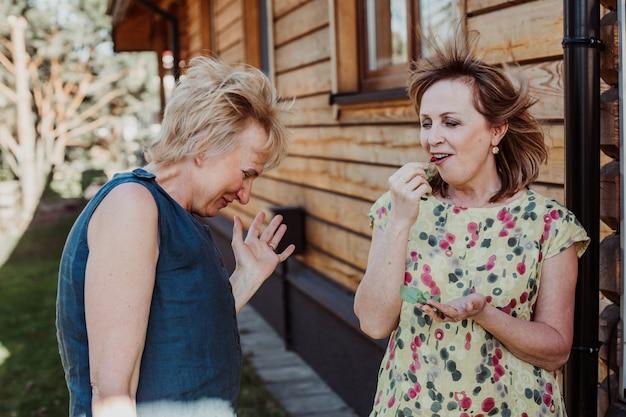 Twee vrouwen van 55 jaar oud praten schattig op de achtergrond van een houten muur