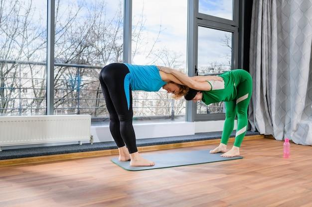Twee vrouwen van middelbare leeftijd oefenen gepaarde yoga fitnesstraining uit, staan op de mat, kantelen met gekruiste handen op elkaars rug