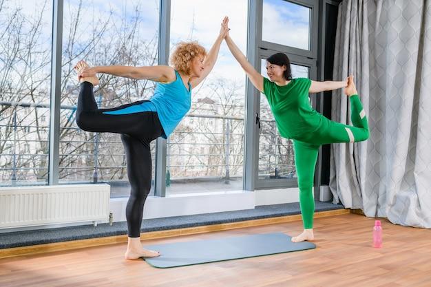 Twee vrouwen van middelbare leeftijd strekken zich uit en balanceren samen, houden elkaars hand vast en staan op één been