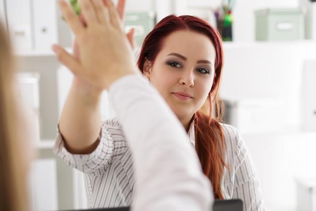 Twee vrouwen vieren iets high five geven op kantoor