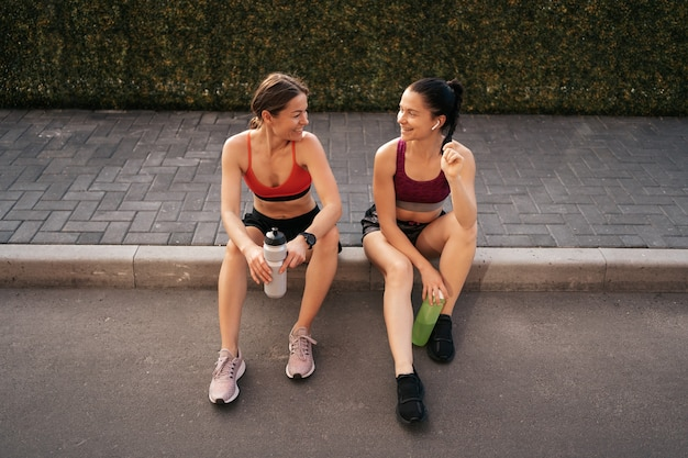 Twee vrouwen voor stedelijke training. meisjes bereiden zich voor om op straat te rennen en te zitten. fitnesspauze