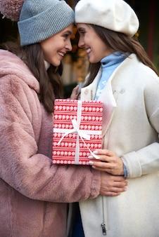 Twee vrouwen wisselen een kerstcadeau uit